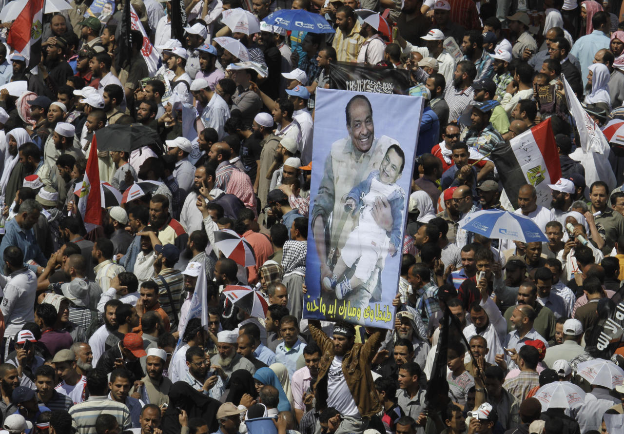 """Egyptian protesters shout anti-military council slogans in front of a banner showing Egypt's military ruler Field Marshal Hussein Tantawi, left, carrying ousted President Hosni Mubarak, during a demonstration at Tahrir Square, the focal point of Egyptian uprising, in Cairo, Egypt, Friday April 20, 2012. Tens of thousands of protesters packed Cairo's downtown Tahrir Square on Friday in the biggest demonstration in months against the ruling military, aimed at stepping up pressure on the generals to hand over power to civilians and bar ex-regime members from running in upcoming presidential elections. Arabic on the banner reads, """"Tantawi and Mubarak are one hand."""" (AP Photo/Amr Nabil)"""