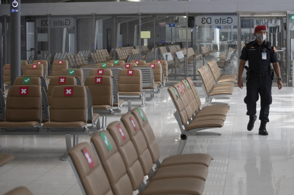 A security person patrols at Suvarnabhumi Airport in Bangkok, Friday, July 3, 2020. As the country starts to ease its travel restrictions allowing foreign visitors in on a controlled basis, a laboratory at the airport will have the results of COVID-19 virus testing ready within 90 minutes for arriving travelers. (AP Photo/Sakchai Lalit)