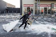 A suspected looter hauls away items on Wednesday from a ransacked shopping mall in Vosloorus on the outskirts of Johannesburg