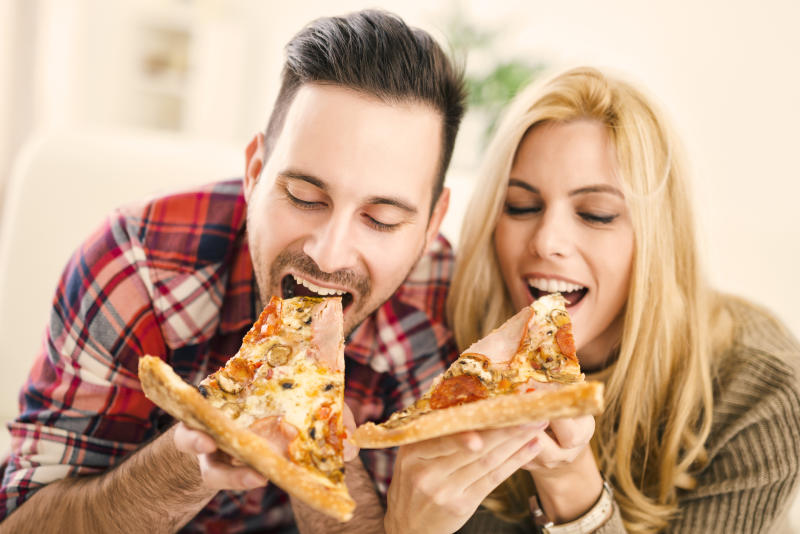 A couple eating pizza.