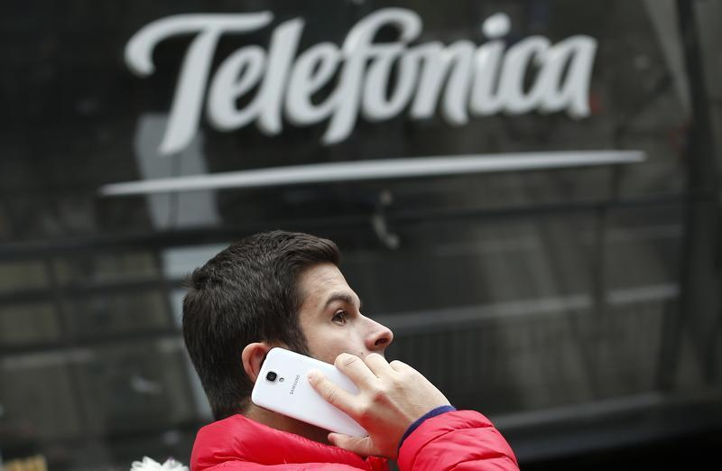 A man talks by mobile phone as he walks past Spanish telecom group Telefonica flagship store in central Madrid