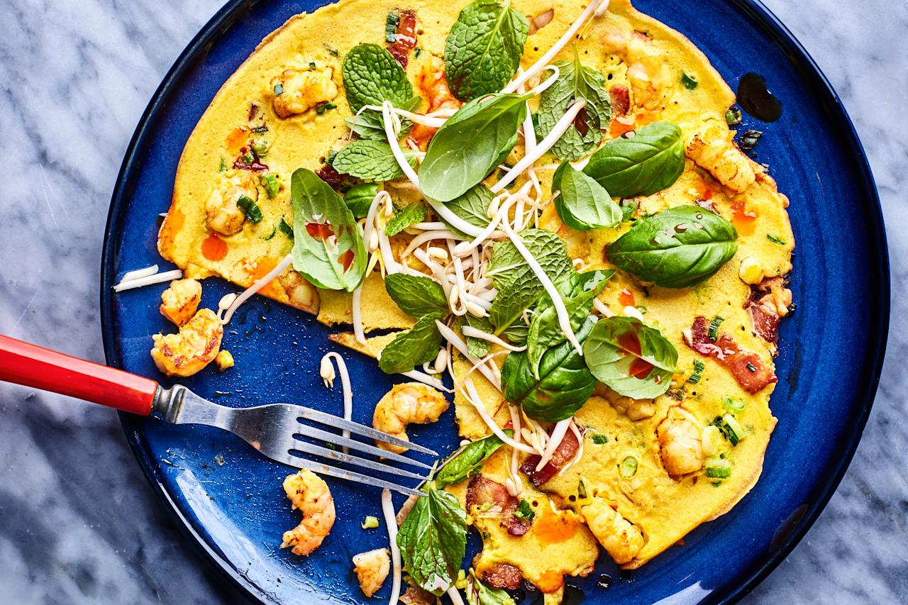 """In this Asian-inspired dinner, the savory, protein-rich pancake is made with chickpea flour and coconut milk, and is studded with bacon, scallions, and turmeric-spiced shrimp. Top it off with fresh herbs and crunchy mung beans and it'll gain a permanent place in your weeknight rotation. <a href=""""https://www.epicurious.com/recipes/food/views/coconut-shrimp-pancakes-with-fresh-herbs?mbid=synd_yahoo_rss"""">See recipe.</a>"""