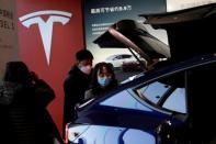 FILE PHOTO: Visitors wearing face masks check a China-made Tesla Model Y sport utility vehicle (SUV) at the electric vehicle maker's showroom in Beijing