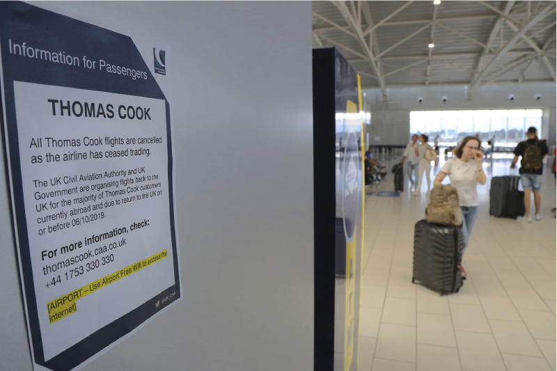 A woman passes by a notice of informations for Thomas Cook passengers is seen on a wall at Larnaca airport in the eastern Mediterranean island of Cyprus, Monday, Sept. 23, 2019. The collapse of tour operator Thomas Cook will strike a major blow to the Cypriot tourism industry. (AP Photo/Petros Karadjias)