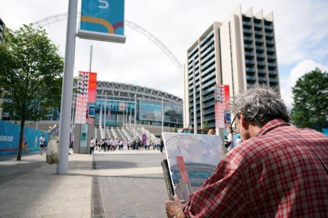 An artist paints a picture of the ground ahead of the Euro 2020 final at Wembley Stadium