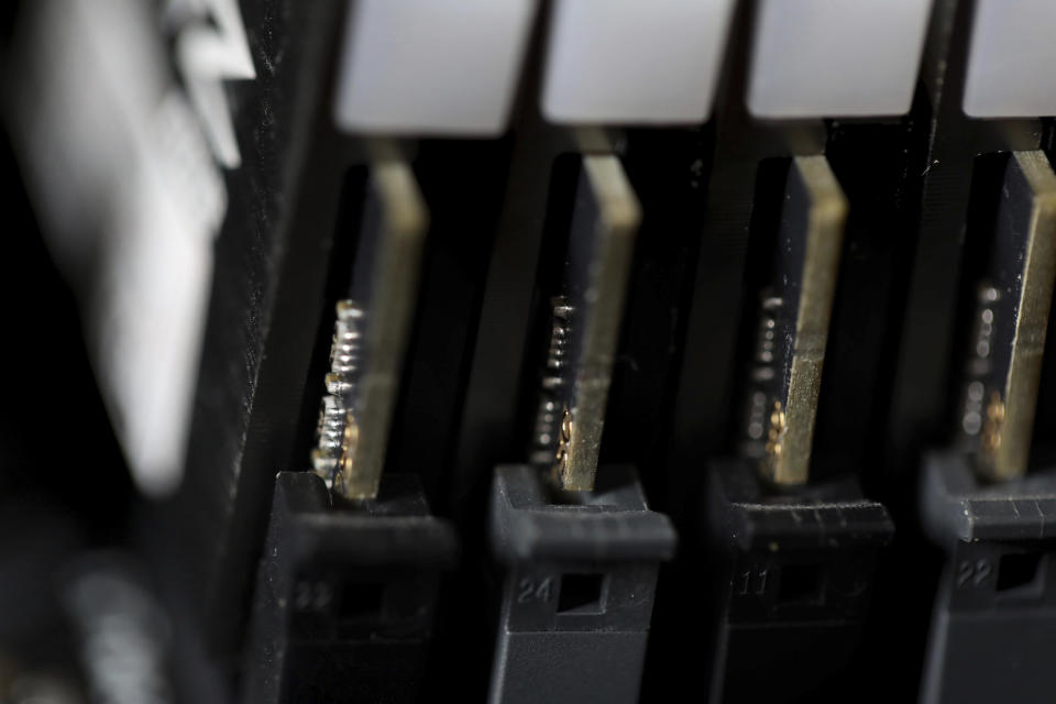 FILE - This Feb 23, 2019, file photo shows the inside of a computer in Jersey City, N.J. Cybersecurity teams worked feverishly Sunday, July 4, 2021, to stem the impact of the single biggest global ransomware attack on record, with some details emerging about how the Russia-linked gang responsible breached the company whose software was the conduit. An affiliate of the notorious REvil gang, infected thousands of victims in at least 17 countries on Friday, largely through firms that remotely manage IT infrastructure for multiple customers, cybersecurity researchers said. (AP Photo/Jenny Kane, File)