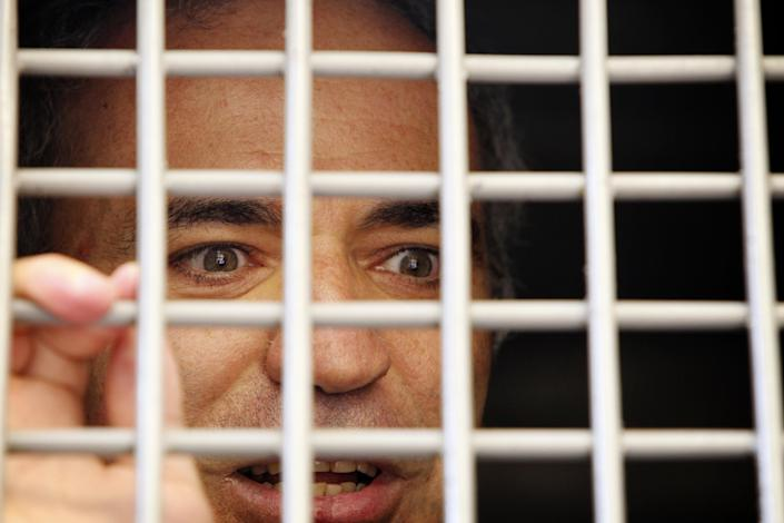 Former world chess champion Garry Kasparov, a leading opposition activist, speaks from a police vehicle after having been detained by police outside the court where a trial of the feminist punk group Pussy Riot is held, in Moscow, Friday, Aug. 17, 2012. A Moscow judge sentenced three members of the provocative punk band Pussy Riot to two years in prison each on hooliganism charges on Friday following a trial that has drawn international outrage as an emblem of Russia's intolerance of dissent. (AP Photo/Yuri Tutov)