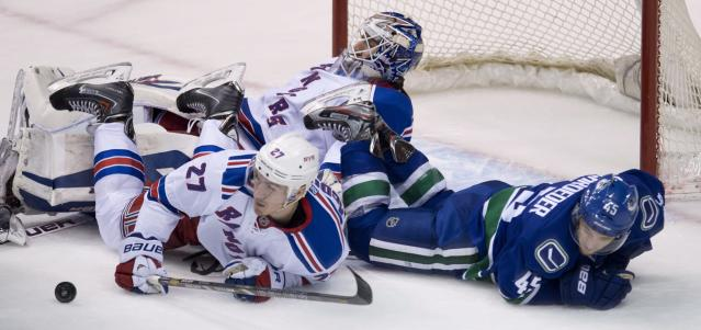 New York Rangers defenseman Ryan McDonagh (27) and Vancouver Canucks center Jordan Schroeder (45) fall over Rangers goalie Henrik Lundqvist (30) during the second period of an NHL hockey game Tuesday, April 1, 2014, in Vancouver, British Columbia. (AP Photo/The Canadian Press, Jonathan Hayward)
