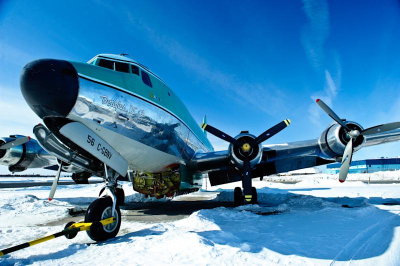 """In this undated image released by The Weather Channel, a Buffalo Airways plane rests on a snow covered tarmac in a promotional photo from """"Ice Pilots,"""" airing Mondays at 9 p.m. EST on The Weather Channel. The Weather Channel is in the midst of a transformation with original programming about Arctic pilots, steel workers, wind turbine and power line repairers and Coast Guard rescuers in both icy and tropical climates. (AP Photo/The Weather Channel)"""