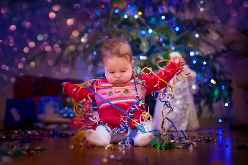 Cute funny baby girl sitting under Christmas tree