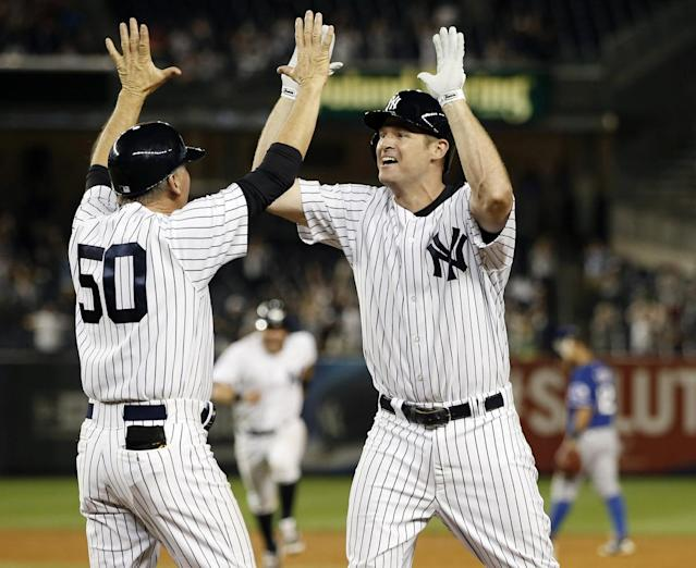 Newly aquired New York Yankees Chase Headley, right, celebrates with New York Yankees first base coach Mick Kelleher (50) after hitting a game-winning, 14th-inning, walk-off, RBI single in the Yankees 2-1 victory over the Texas Rangers in a baseball game at Yankee Stadium in New York, Wednesday, July 23, 2014. (AP Photo)