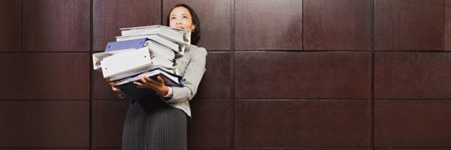 A woman holding heavy binders