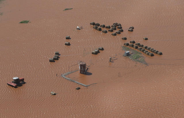 Hay bales and equipment are pictured in a flooded field, Tuesday, May 21, 2019, in Kingfisher, Okla. Flooding following heavy rains was an issue across the state. (AP Photo/Sue Ogrocki)