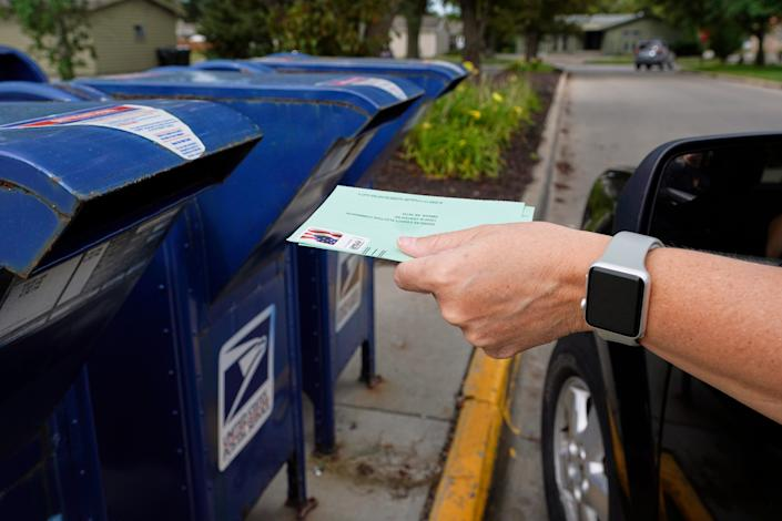 Dropping application for mail-in ballot into a mail box in Omaha, Nebraska, on Aug. 18, 2020.