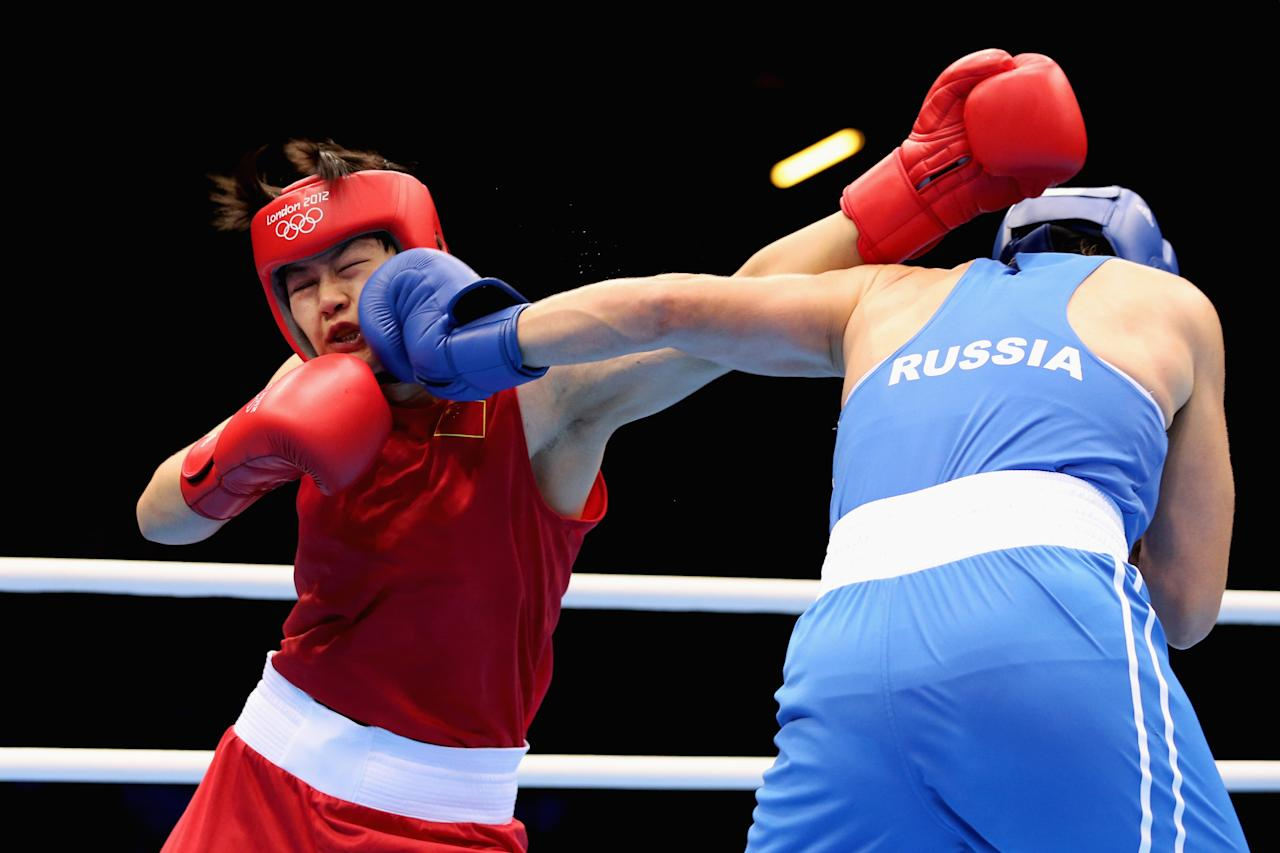 LONDON, ENGLAND - AUGUST 08:  Nadezda Torlopova (R) of Russia in action against Jinzi Li of China during the Women's Middle (75kg) Boxing semifinals on Day 12 of the London 2012 Olympic Games at ExCeL on August 8, 2012 in London, England.  (Photo by Scott Heavey/Getty Images)