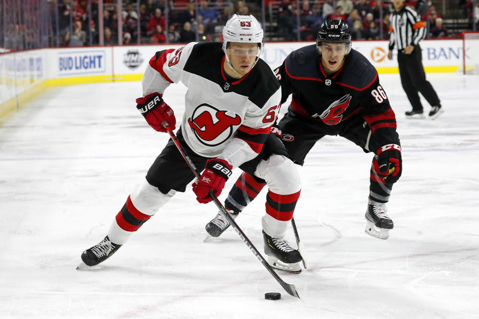 New Jersey Devils' Jesper Bratt (63), of Sweden, protects the puck from Carolina Hurricanes' Teuvo Teravainen (86), of Finland, during the first period of an NHL hockey game in Raleigh, N.C., Friday, Feb. 14, 2020. (AP Photo/Karl B DeBlaker)