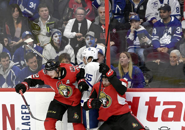 Ottawa Senators defenseman Thomas Chabot (72) and left wing Nick Paul (13) pin Toronto Maple Leafs center Alexander Kerfoot (15) along the boards during second-period NHL hockey game action in Ottawa, Ontario, Saturday, Feb. 15, 2020. (Justin Tang/The Canadian Press via AP)