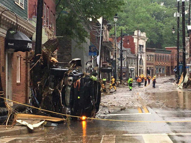 <p>Rescue personnel walk along Ellicott City's Main Street. (Photo: Libby Solomon, Baltimore Sun via AP) </p>