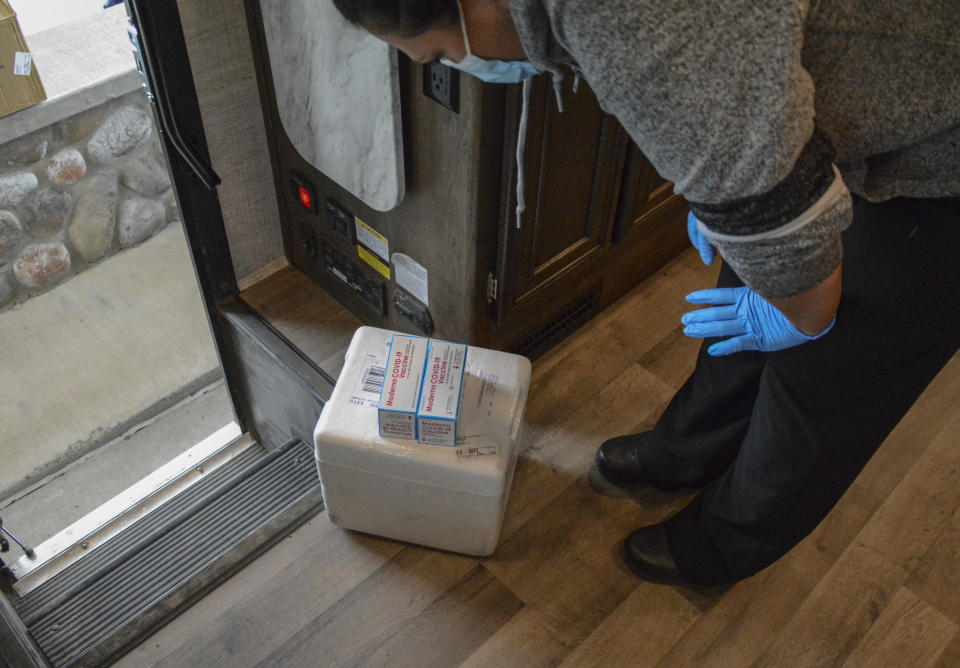 In this Thursday, April 29, 2021, photo, a Blackfeet tribe nurse examines a delivery of Moderna and Pfizer COVID-19 vaccines that will be given to Canadian residents at the Piegan-Carway border crossing near Babb, Mont. The Blackfeet tribe gave out surplus vaccines to its First Nations relatives and others from across the border. (AP Photo/Iris Samuels)
