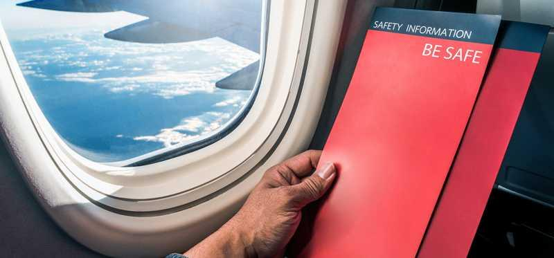 Passenger reading plane safety manual as he sits in a window seat.
