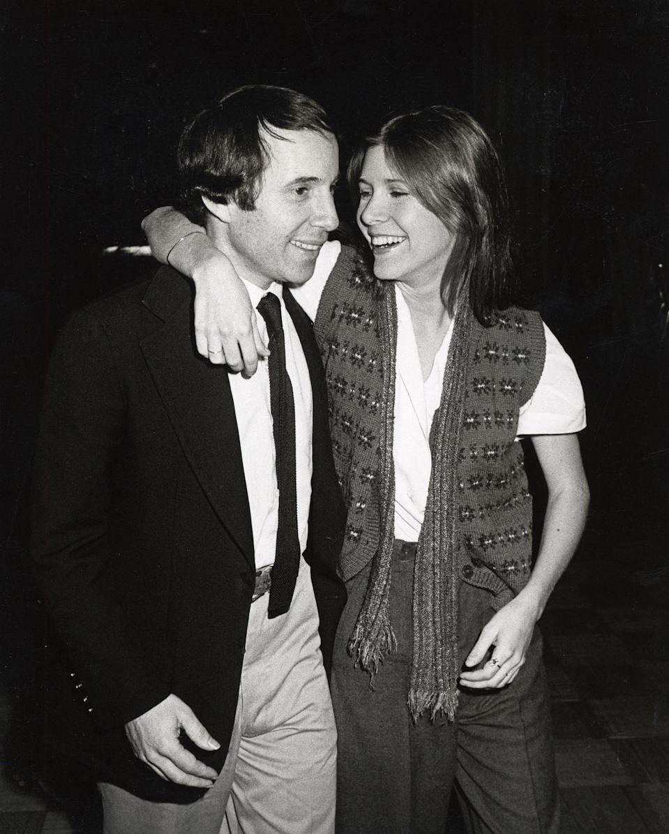 "<p>In 1977, Carrie began dating singer Paul Simon, after meeting on the set of <em>Star Wars</em>. The pair dated on and off for the next six years, with Carrie <a href=""https://soaphub.com/entertainment/real-life-celebrity-breakup-carrie-fisher-and-paul-simon/"" rel=""nofollow noopener"" target=""_blank"" data-ylk=""slk:breaking off an engagement"" class=""link rapid-noclick-resp"">breaking off an engagement</a> with her <em>The </em><em>Blues Brothers</em> costar Dan Aykroyd to reconcile with Paul in 1980. </p>"