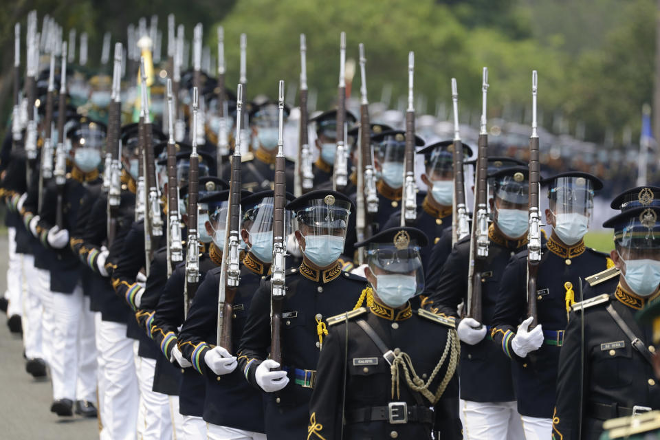 Honor guards march during the state burial rites of former Philippine President Benigno Aquino III on Saturday, June 26, 2021 at a memorial park in suburban Paranaque city, Philippines. Aquino was buried in austere state rites during the pandemic Saturday with many remembering him for standing up to China over territorial disputes, striking a peace deal with Muslim guerrillas and defending democracy in a Southeast Asian nation where his parents helped topple a dictator. He was 61. (AP Photo/Aaron Favila)