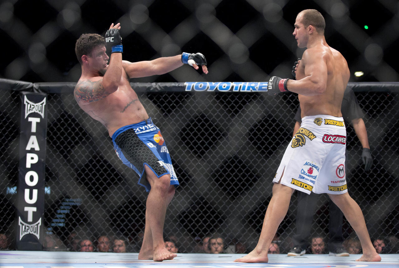 Frank Mir, left, falls backward after Junior Dos Santos landed a punch in the second round during a UFC 146 heavyweight title bout, Saturday, May 26, 2012, in Las Vegas. Dos Santos won by knockout. (AP Photo/Julie Jacobson)
