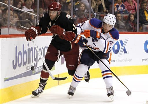 Phoenix Coyotes' Keith Yandle (3) and Edmonton Oilers' Taylor Hall (4) battle for the puck in the first period in an NHL hockey game Thursday, Dec. 15, 2011, in Glendale, Ariz.(AP Photo/Ross D. Franklin)