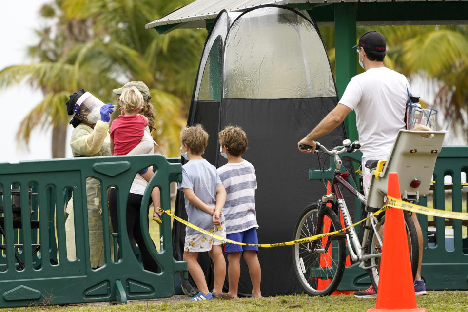 A health care worker, left, administers a COVID-19 test at a mobile walk-up testing site at Crandon Park, Saturday, Nov. 28, 2020, in Miami. (AP Photo/Lynne Sladky)
