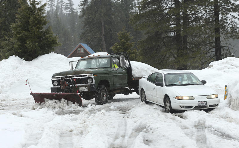 File - In this Feb. 28, 2019, file photo, snow, from recent storms, is cleared from the parking lot of the Strawberry Lodge at Strawberry, Calif. A cold front traveling down to Northern California from the Gulf of Alaska is expected to dump at least a foot of snow in higher elevations of the Sierra Nevada weeks before the start of summer. National Weather Service meteorologist Brendon Rubin-Oster says the first storm will arrive Wednesday, May 15, 2019, and will continue through Thursday. (AP Photo/Rich Pedroncelli, File)