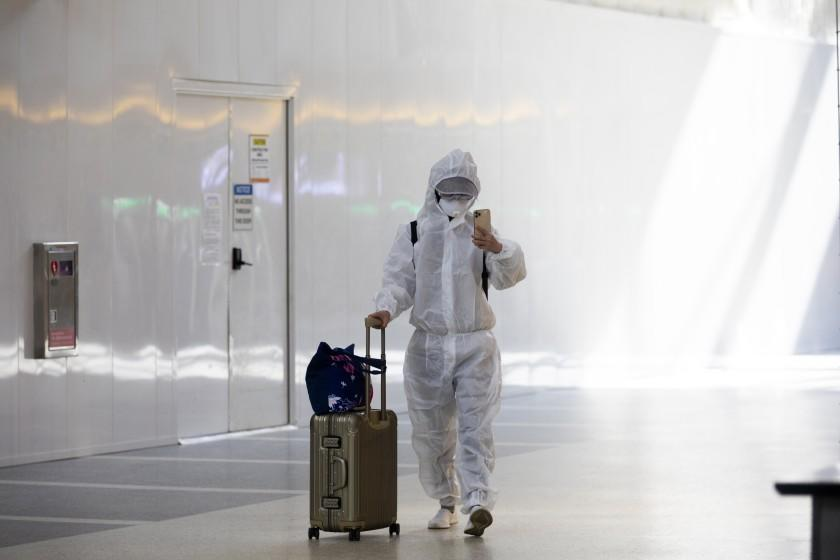 LOS ANGELES, CA - NOVEMBER 17: During the global coronavirus pandemic a pasanger wearing personal protective equipment walks in Tom Bradley international at LAX on Tuesday, Nov. 17, 2020 in Los Angeles, CA. Los Angeles International Airport will begin issuing molecular or PCR tests in two terminals this week and has plans to quickly expand the program in order to help detect coronavirus and slow its spread. (Francine Orr / Los Angeles )