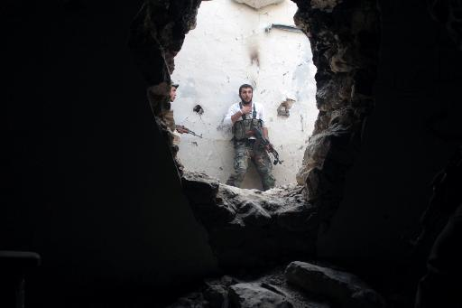 Rebel fighters hold a position in a damaged building during clashes with Syrian government forces in the northeastern city of Deir Ezzor, on November 11, 2013