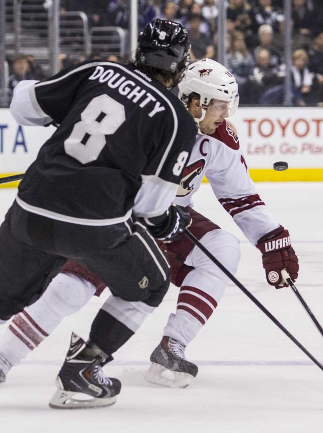 Los Angeles Kings defenseman Drew Doughty (8) and Phoenix Coyotes forward Shane Doan (19) vie for the puck during the first period of an NHL hockey game, Wednesday, April 2, 2014, in Los Angeles. (AP Photo/Ringo H.W. Chiu)