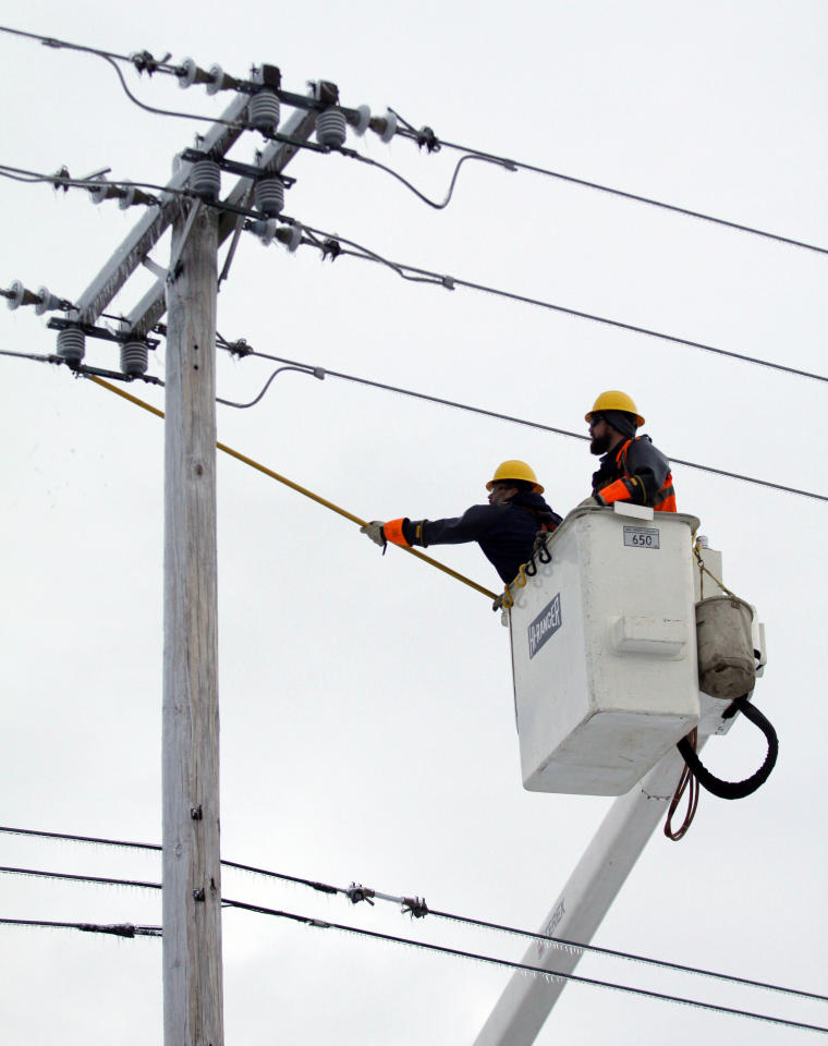 Eric Sheffer, left, and Matt Adams reconnect a power line, Thursday, Dec. 26, 2013, in East Lansing, Mich. The two are from the City of Hillsdale, Michigan's Board of Public Utilities brought in to assist the Lansing Board of Water and Light with restoring power in Michigan after an ice storm. (AP Photo/Al Goldis)