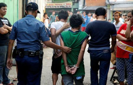 Policemen escort two men who were detained because of pending criminal court cases, during an anti-drugs operation in Mandaluyong, Metro Manila in the Philippines, November 10, 2016. REUTERS/Erik De Castro