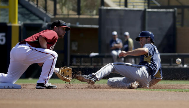Milwaukee Brewers' Scooter Gennett, right, is tagged out at second by Arizona Diamondbacks second baseman Aaron Hill after trying to steal during the first inning of a spring exhibition baseball game in Scottsdale, Ariz., Sunday, March 16, 2014. (AP Photo/Chris Carlson)