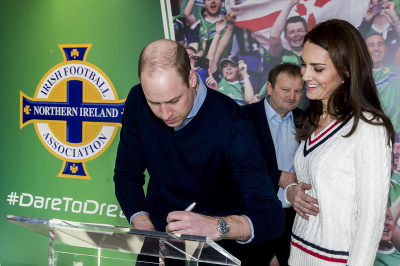 The Duke and Duchess of Cambridge signing the visitors book during their visit to Windsor Park, Belfast as part of their two day visit to Northern Ireland.