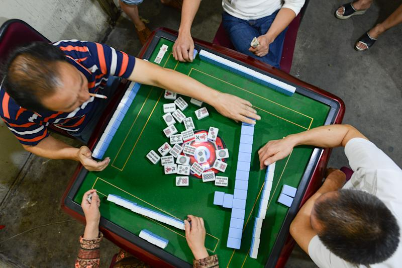 People enjoy a party of Mahjong, a traditional game played by four players, with a set of 144 tiles based on Chinese characters and symbols, in Liling. On Thursday, September 22, 2016 in Liling, Zhuzhou, Hunan Province, China. (Photo by Artur Widak/NurPhoto via Getty Images)