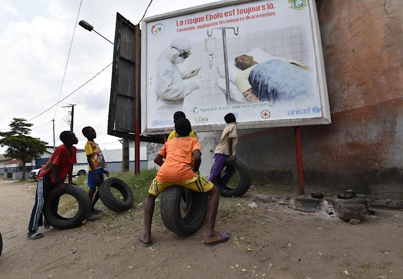 Children look at a poster warning of the dangers of the Ebola virus on August 24, 2014 in Abidjan, Ivory Coast