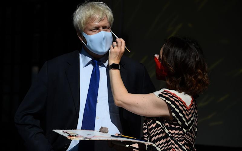An artist puts the finishing touches to a wax figure of Prime Minister Boris Johnson, in the entrance line at Madame Tussaud's - Kirsty O'Connor/PA