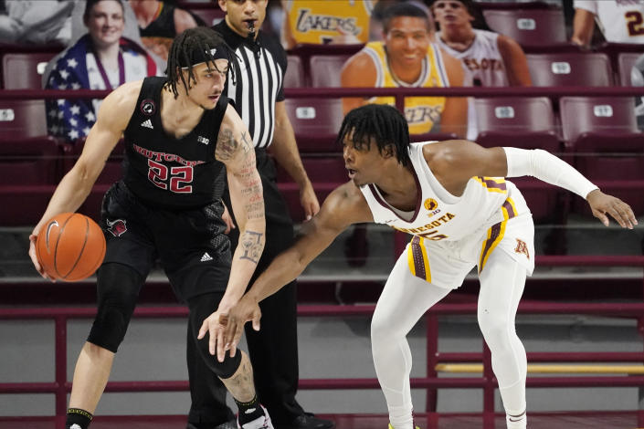 Rutgers' Caleb McConnell (22) keeps an eye on Minnesota's Marcus Carr (5) in the first half of an NCAA college basketball game, Saturday, March 6, 2021, in Minneapolis. (AP Photo/Jim Mone)