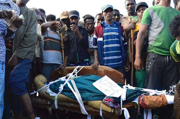 People standing next to the body of a protester from the Oromo group allegedly shot dead by security forces in Wolenkomi, west of Addis Ababa (AFP Photo/William Davison)