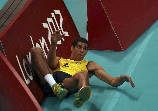 Brazil's Wallace de Souza crashes into the barrier during their men's Group B volleyball match against Tunisia at the London 2012 Olympic Games at Earls Court July 29, 2012.