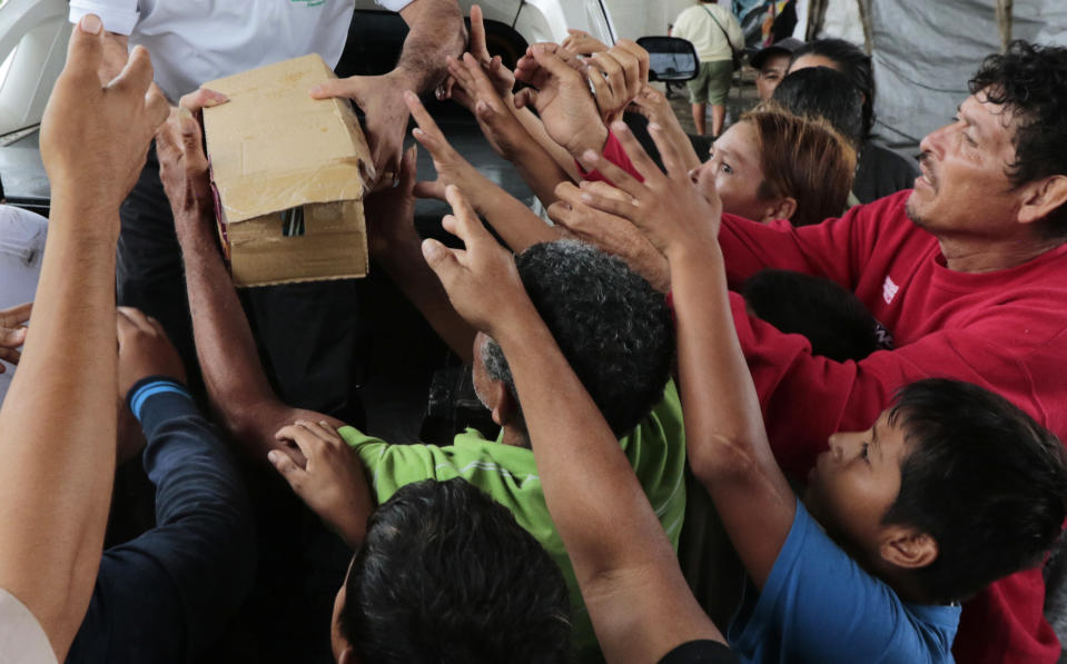 A person distributes food to hurricane victims under a bridge in San Pedro Sula, Honduras, Saturday, Nov. 21, 2020. Shelters for people whose homes were flooded or damaged by hurricanes Eta and Iota in Honduras are now so crowded that thousands of victims have taken refuge under highway overpasses or bridges. The Red Cross estimates that about 4.2 million people were affected by the back-to-back hurricanes in November in Honduras, Nicaragua and Guatemala. (AP Photo/Delmer Martinez)