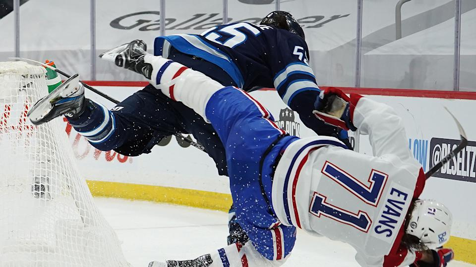 WINNIPEG, MB - JUNE 2: Jake Evans #71 of the Montreal Canadiens is left injured after scoring a third period empty net goal and then checked hard by Mark Scheifele #55 of the Winnipeg Jets in Game One of the Second Round of the 2021 Stanley Cup Playoffs on June 2, 2021 at Bell MTS Place in Winnipeg, Manitoba, Canada. (Photo by David Lipnowski/Getty Images)