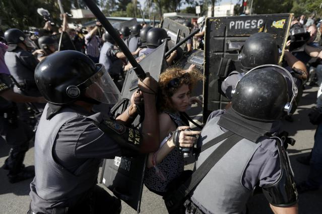 A woman is pushed by riot policemen during a clash with demontrators in a protest against the 2014 World Cup in Sao Paulo June 12, 2014. REUTERS/Ricardo Moraes (BRAZIL - Tags: SPORT SOCCER WORLD CUP CIVIL UNREST)