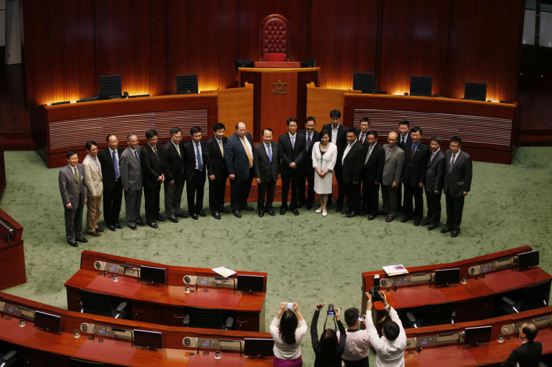 Beijing's top representative in Hong Kong, Zhang Xiaoming poses with the lawmakers at a chamber, during the first meeting between the head of the central government's liaison office and the full membership of Hong Kong's Legislative Council in Hong Kong Tuesday July 16, 2013. Beijing's top representative in Hong Kong met Tuesday with local lawmakers to ease tensions between the mainland and its special administrative region, though he warned against a planned protest and said Hong Kongers will never get to nominate their own leadership candidates without central government approval. (AP Photo/Kin Cheung)