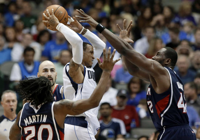 Dallas Mavericks point guard Monta Ellis, center, attempts to pass the ball under pressure from Atlanta Hawks' Cartier Martin (20), Elton Brand, right, and Pero Antic, rear, of Macedonia, in the first half of an NBA preseason basketball game Wednesday, Oct. 23, 2013, in Dallas. (AP Photo/Tony Gutierrez)
