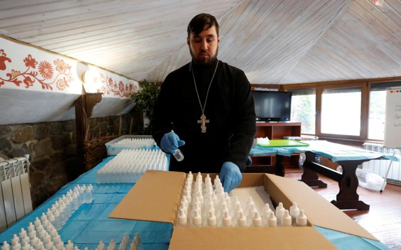 A clergyman of the Orthodox Church of Ukraine packs bottles of hand sanitizer at the Vydubychi Monastery in Kiev, Ukraine  - REUTERS
