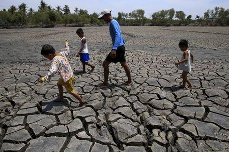 A father with his children walk over cracked soil of a 1.5 hectare dried up fishery at the Novaleta town in Cavite province, south of Manila